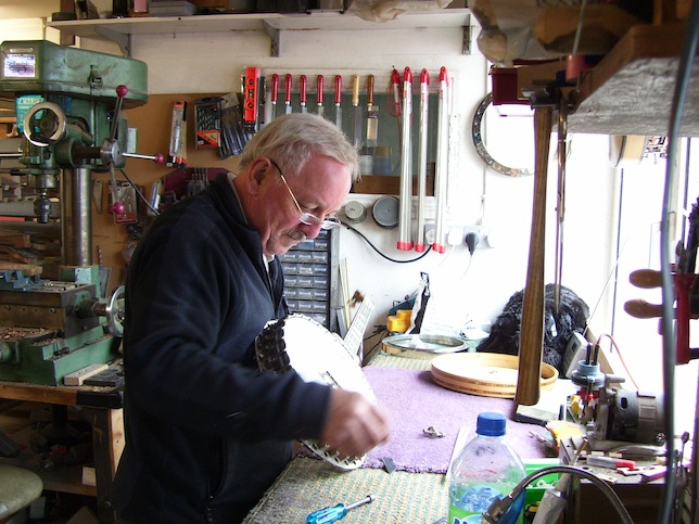 Tom Cussen working on a banjo in his workshop